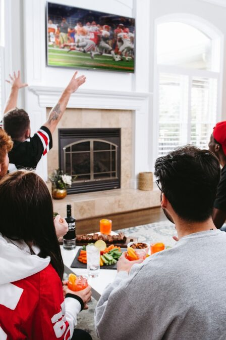 People cheering at television for a tampa super bowl watch party